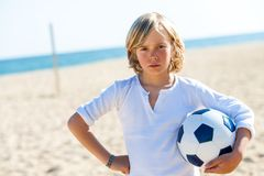 Upset boy holding soccer ball outdoors. Portrait of unhappy boy with soccer ball on beach Stock Photography