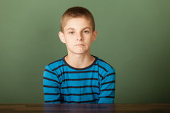 Upset boy looking at camera. Young boy with short hair sadly looking at camera wearing blue t-shirt sitting at desk over green chalkboard background Royalty Free Stock Image