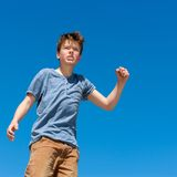 Upset boy raising fist outdoors. Stock Images