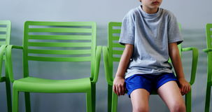 Upset boy sitting on chair in hospital corridor. Upset boy sitting on chair in corridor at hospital stock video footage