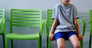 Upset boy sitting on chair in hospital corridor stock video footage