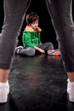 Upset boy sitting on floor with man on foreground. On black Stock Photography