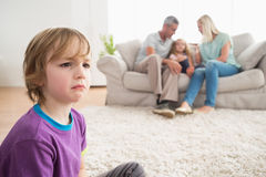 Upset boy sitting on floor while parents enjoying with sister Stock Photos