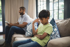 Upset boy sitting on sofa with father holding digital tablet at home. Upset boy sitting on sofa with father holding digital tablet in background at home stock image