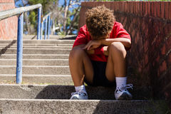 Upset boy sitting on staircase in the boot camp. On a sunny day Stock Photography