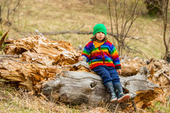 Upset boy sitting on tree trunk Royalty Free Stock Photos