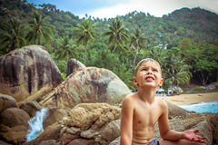 Upset boy waits for the rain on beach of tropical Stock Images