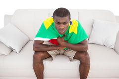 Upset brazilian football fan sitting on couch Royalty Free Stock Photos