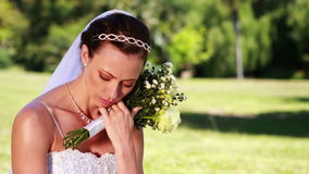 Upset bride sitting on the grass. On her wedding day stock video