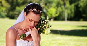 Upset bride sitting on the grass. On her wedding day stock video footage