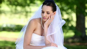 Upset bride sitting on the grass. On a sunny day stock video