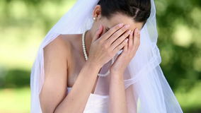 Upset bride sitting on the grass. On a sunny day stock video footage