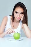 Upset brunette woman with green apple on a plate Stock Images