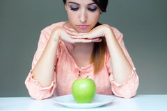 Upset brunette woman with green apple on a plate Stock Photo