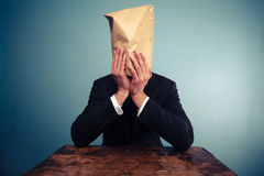 Upset businesman with bag over his head Royalty Free Stock Image