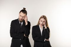 Upset business couple wearing black suits over white background, working together stock images
