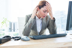 Upset business woman with head in hands in front of computer at office stock image