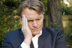 Upset businessman. A distraught and emotional businessman sitting in the park thinking things through Stock Images
