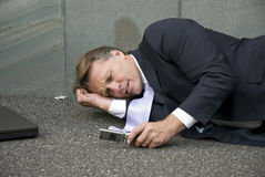 Upset businessman. A distraught and emotional businessman is laying on the ground after receiving bad news on his cellphone Royalty Free Stock Photos