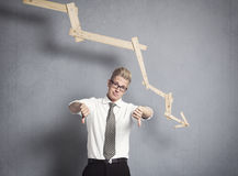 Upset businessman in front of descending graph. Royalty Free Stock Photo