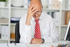 Upset Businessman With Hand On Head At Desk. Upset mature businessman with hand on head sitting at office desk Royalty Free Stock Photos