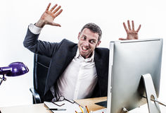 Upset businessman having a corporate tantrum at his computer desk. Raising his hands for exasperation, stress and nervous crisis, contrast effects, white Stock Photos