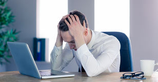 Upset businessman with head in hands Royalty Free Stock Photography