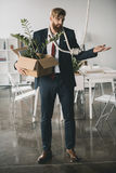 Upset businessman holding box with belongings and trying to hang himself. Young upset businessman holding box with belongings and trying to hang himself Stock Photography