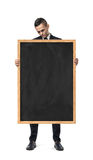 Upset businessman holds an empty blackboard isolated on the white background Royalty Free Stock Photos