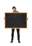Upset businessman holds an empty blackboard isolated on the white background Royalty Free Stock Photo