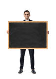 Upset businessman holds an empty blackboard isolated on the white background. An upset businessman holds an empty blackboard isolated on the white background Stock Images