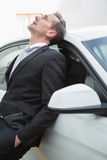 Upset businessman leaning on his car Stock Photos