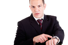Upset businessman pointing to the watch. Isolated on white background. Studio shot Stock Images