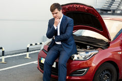 Upset businessman sitting on bonnet of broken car Stock Photo