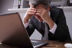 Upset Businessman Sitting In Office. With Laptop On Wooden Desk stock photography