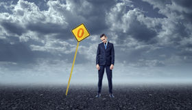 Upset businessman standing on rocky ground in front of yellow road sign with zero. An upset businessman standing on a rocky ground in front of a yellow road sign Royalty Free Stock Photo