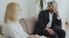 Upset businessman talking about his porblems with female psychologist. In office indoors stock footage