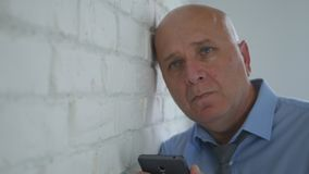Upset Businessman Thinking Disappointed with Cell Phone in Hand stock photo