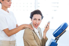 Upset businesswoman having back massage Stock Photos