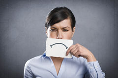 Upset businesswoman holding blank white card in front of her mouth. Stock Photography