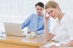Upset businesswoman with man working on laptop Stock Photos