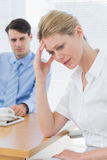 Upset businesswoman with man working on laptop Royalty Free Stock Photography