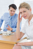 Upset businesswoman with man working on laptop Royalty Free Stock Images