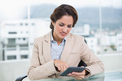 Upset businesswoman using calculator Stock Photo