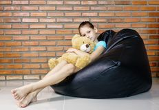 Upset caucasian teen girl sitting in black bean bag chair holding soft teddy bear toy against brick wall. Casual outfit. Child. Hood concept stock photo