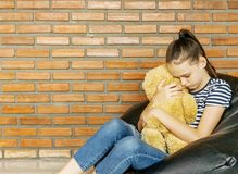 Upset caucasian teen girl sitting in black bean bag chair hug big brown teddy bear toy against brick wall. Casual outfit. Sadness. Problem concept royalty free stock photos
