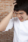 Upset Chef. Asian young chef pose upset, or headache Royalty Free Stock Photo