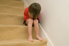 Upset child. Sitting on stairs with his head in his hands Royalty Free Stock Photos