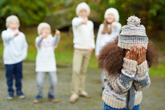 Upset child. African-american girl expressing deep upset while several kids bullying her Stock Photo