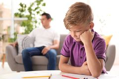 Upset child and blurred father on background royalty free stock photos